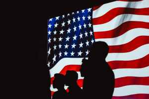 Silhouettes of soldiers standing at attention in front of the American flag