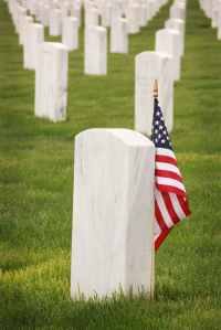 Arlington memorial grave stones with single American flag standing by one of the grave stones