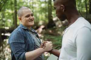 White man and black man shaking hands in the woods