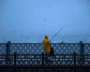 Man in a yellow raincoat standing on a bridge fishing in the rain, waiting for that first bite