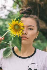 Teenage girl holding a sunflower up to one eye