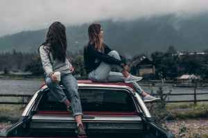 Two teenage girls sitting on the roof of a car looking off in the distance
