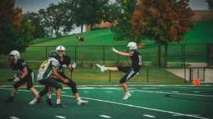 Punter on football team kicking ball