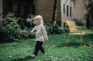 Small blonde child walking in back yard