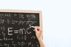 Showing a person's hand writing equations including E=MC2