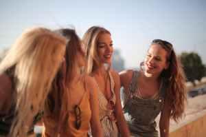 Four teenage girls talking and laughing