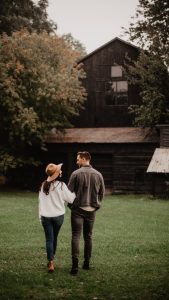 Man and woman walking arm in arm to cabin in the woods