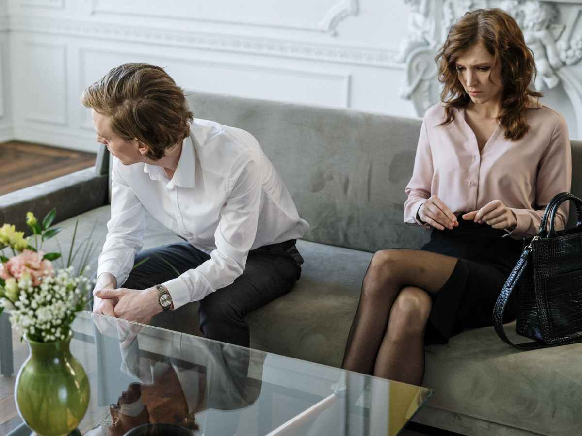 woman in white dress shirt sitting beside woman in white long sleeve shirt