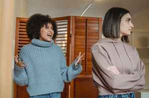 Black girl making fun of white girl who has turned away