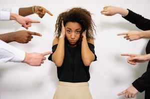 Lady with her hands over her ears while a bunch of hands are pointing at her from both sides
