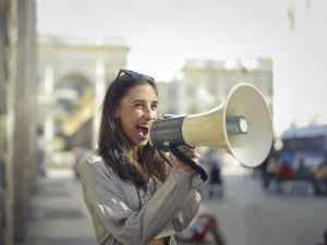 Lady with a smile talking in bullhorn