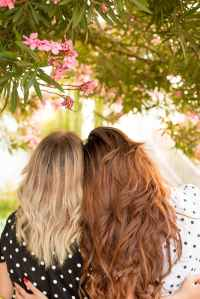 Two women, one blonde and one red head with arms around each other looking in the distance